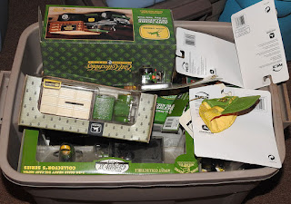 A storage bin full of John Deere collectible toys.