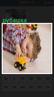 на полу играет ребенок в рубашке с желтой машинкой игрушкой