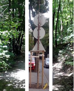 Egy csenevész nagyvárosi fán három közlekedési tábla látszik hátulról, behajtani tilos, főútvonal vége, gyalogátkelőhely, mellette szürke autó halad.