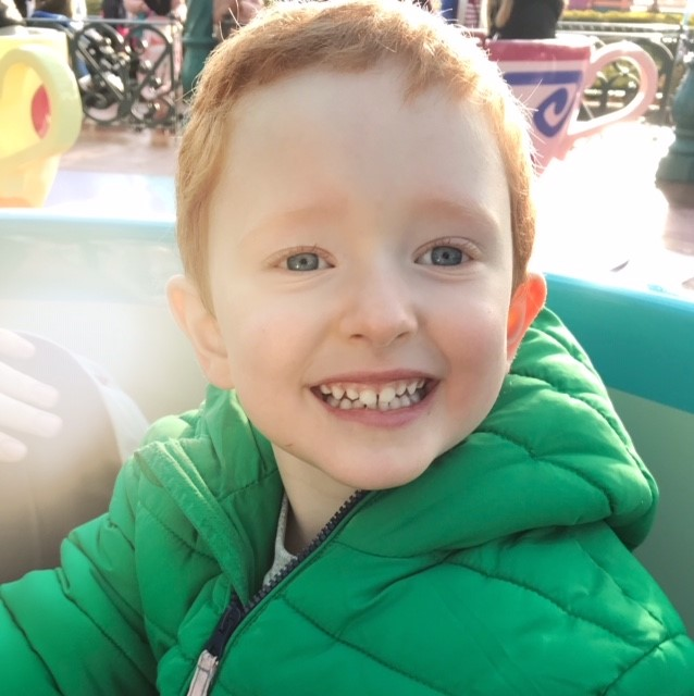 Little boy smiling on a tea cup ride