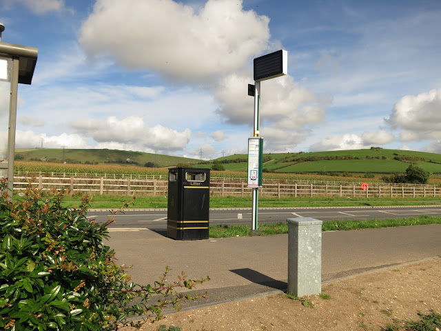 Bus stop, shelter and empty digital sign with open country and sky in background.