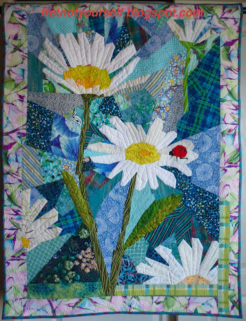 Red ladybug on daisy petal against blue background in this original art quilt.