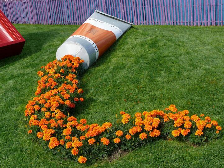 Caléndulas salen de un enorme tubo de pintura naranja en una vibrante instalación