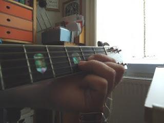 Foto af hånd på guitarens gribebræt