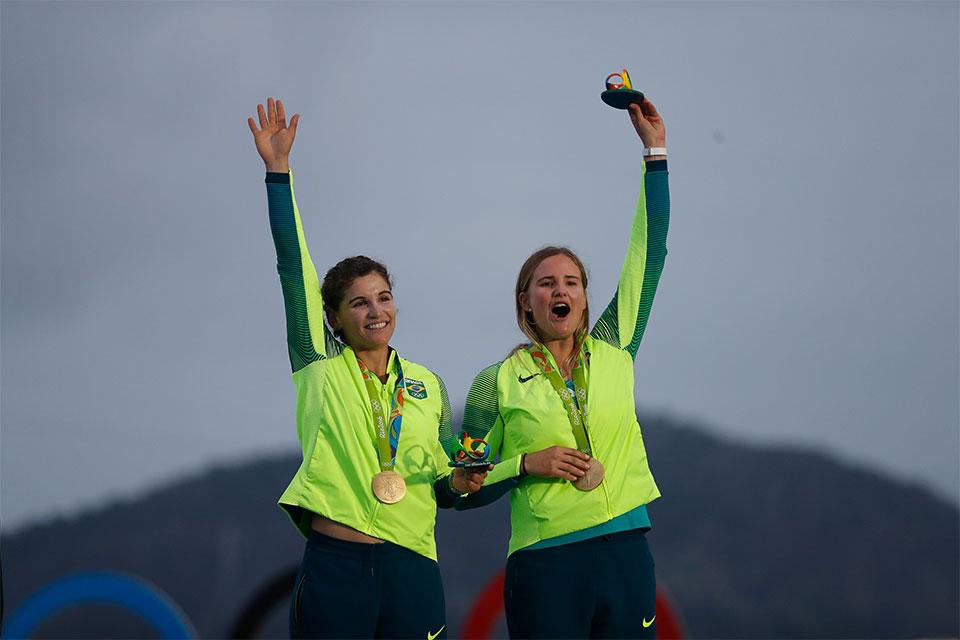 Martine Grael e Kahena Kunze exibem as medalhas de ouro e festejam a vitória na classe 49er FX da vela dos Jogos Olímpicos Rio 2016, na Baía de Guanabara. Foto: Fernando Frazão/Agência Brasil