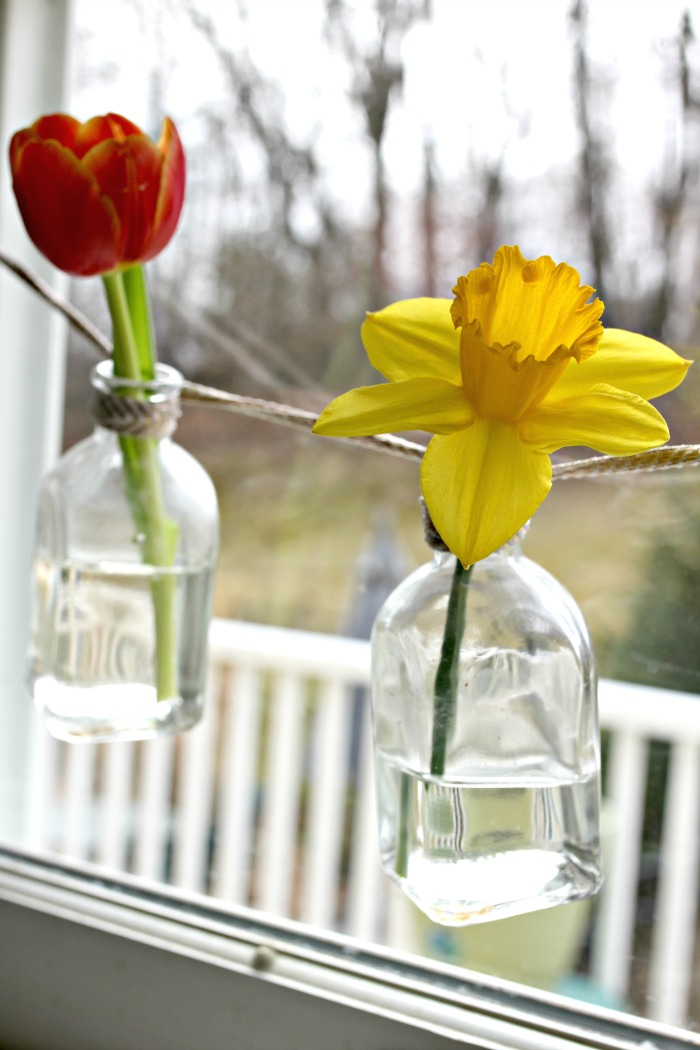 Spring flowers displayed in small vase garland made with glass bottles - www.goldenboysandme.com