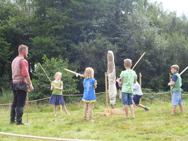 children at a medieval festival learning sword skills