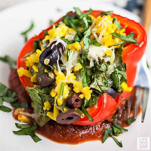 Red pepper stuffed with orzo pasta, spinach, & olives and topped with parmesan cheese on a white plate - Vegetable Stuffed Peppers with Orzo Pasta