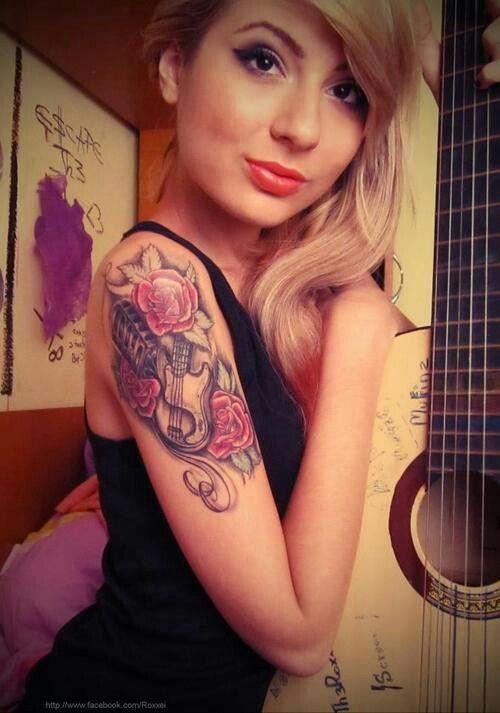 Chica rubia posando lleva un tatuaje de rosa con guitarra