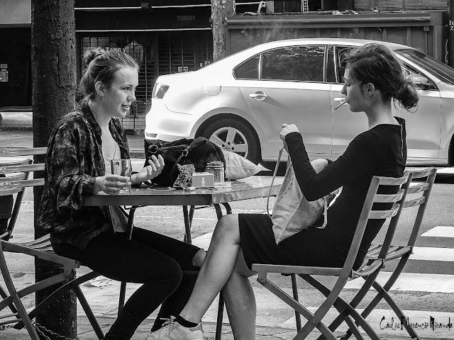 Blanco y  Negro.dos jóvenes sentadas en una mesa de bar en la vereda charlando.