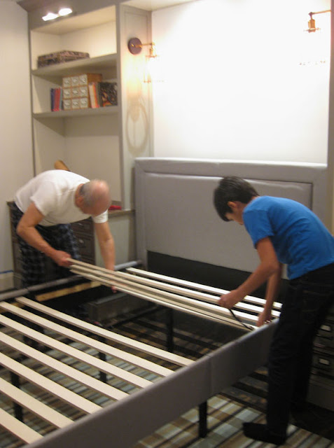 boy and father setting up an upholstered platform bed in boy's room