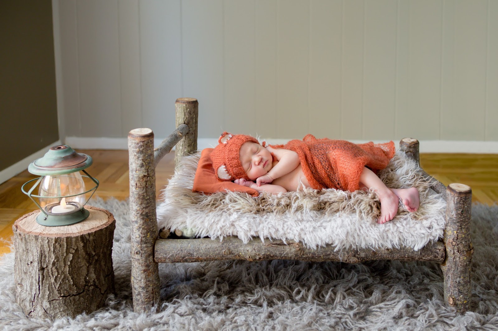 newborn dressed as a fox in log bed