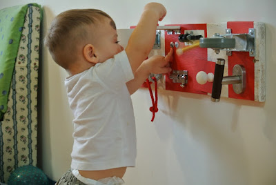 one year old boy playing with a red-and-white sensory board