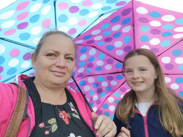mother and tween daughter under umbrellas