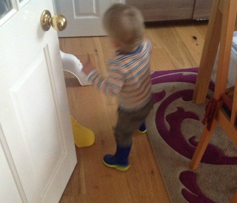 toddler wearing his wonderful wellies in the dining room