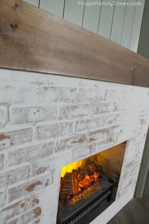 faux brick fireplace with wood mantle