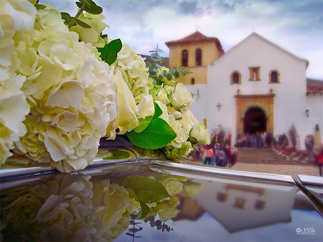 Flores sobre carro matrimonial y al fondo la iglesia principal de Villa de Leyva