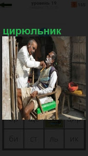 На улице на выходе из помещения цирюльник бреет посетителя мужчину