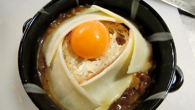 耐熱用の器に炒めた玉ねぎ等を入れ、フランスパン、チーズをのせて最後に生卵をのせる