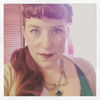 Bridget Eileen as a redhead pin up with Bettie Bangs and Side curled ponytail