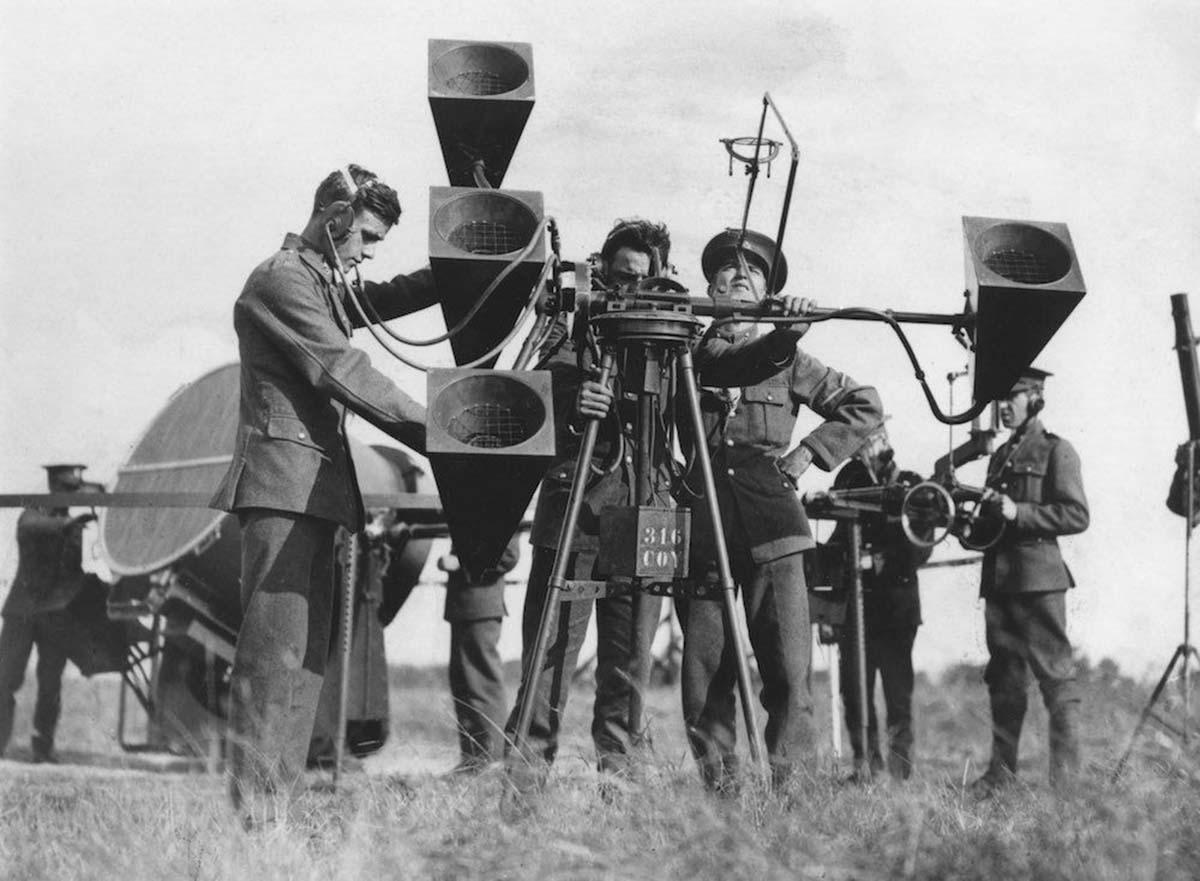 Un localizador acústico de cuatro bocinas nuevamente, en Inglaterra, en la década de 1930. Hay tres operadores, dos con estetoscopios conectados a pares de bocinas para escuchar en estéreo.