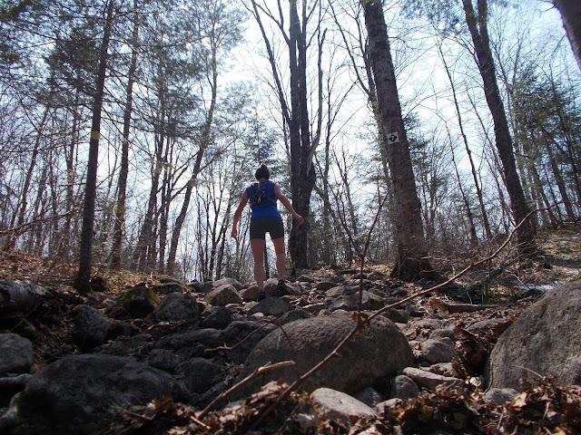 Femme gravissant un sentier de grosses roches