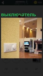 На стене в комнате установлен выключатель белого цвета