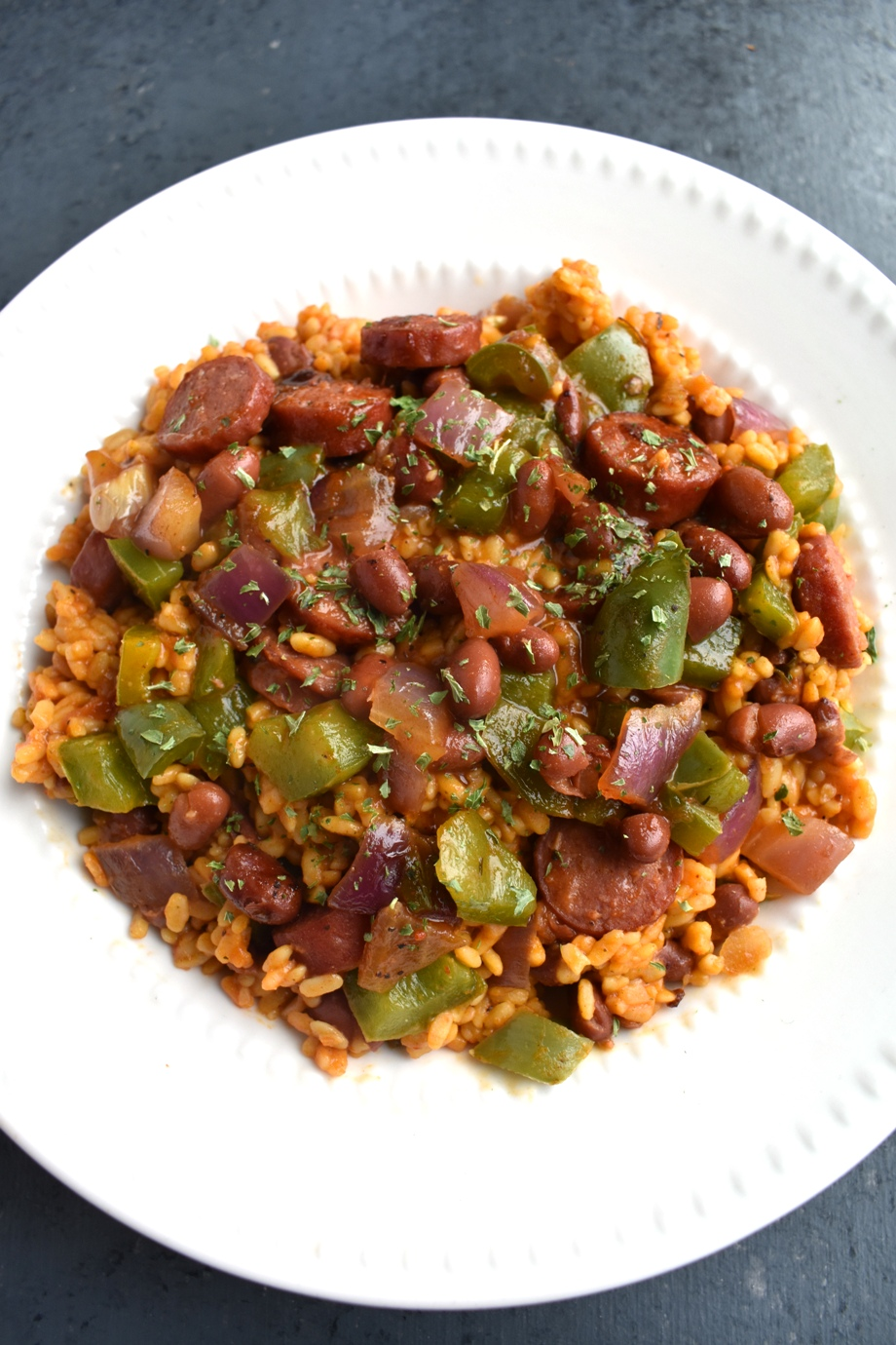 Sausage, Red Beans and Rice is a healthier take on the tradition dish and is loaded with spicy cajun flavor, spicy andouille sausage, sauteed bell peppers, garlic and onions, brown rice and red beans for a healthy and hearty meal!