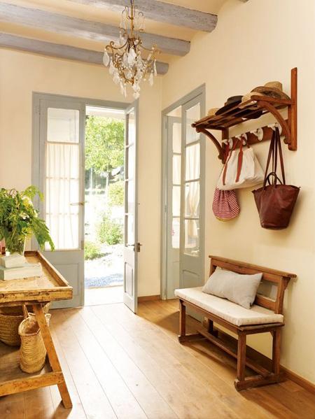 Hall de entrada com cabideiro e banco rústicos em madeira