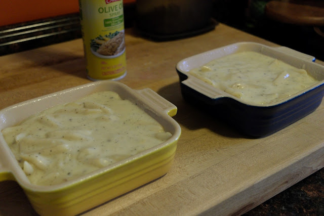 The pasta with the cheese sauce being added to the greased baking dishes.