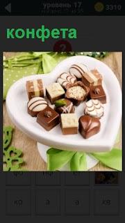 В коробке в виде сердца лежат кондитерские изделия конфеты с разной начинкой