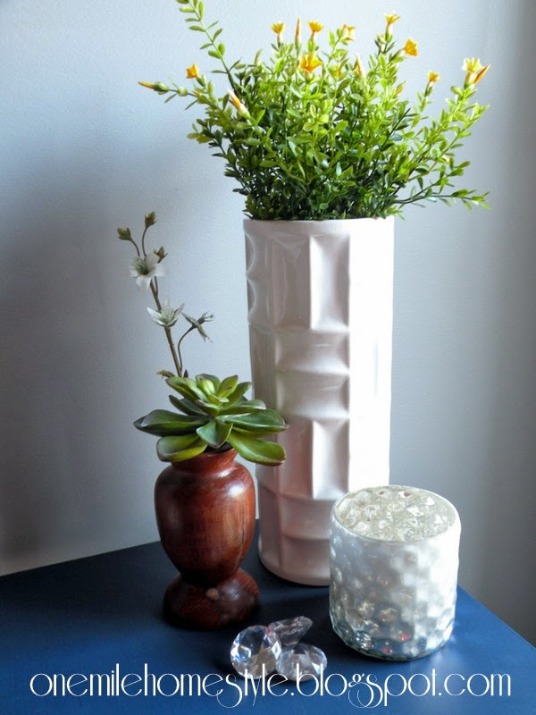 White and wood vases with spring greenery on a navy table