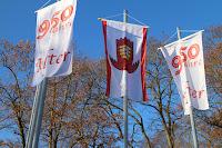 """Zwei Fahnen mit der Aufschrift """"950 Jahre Alfter"""" rahmen die Fahne mit dem Ortswappen ein."""