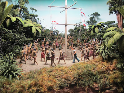 Diorama of a group of 19th-century Maori  around a flagpole in the bush