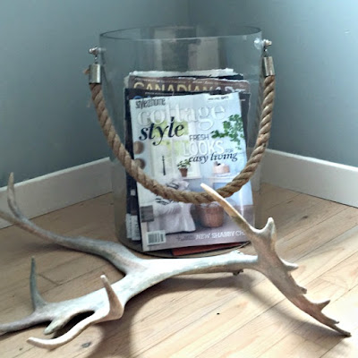 glass container with rope, antler, bleached wood floor