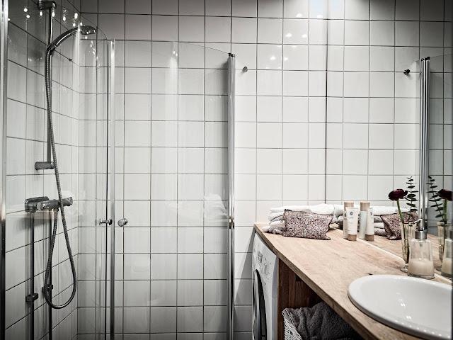 kwadratowe kafelki, kabina prysznicowa, drewniany blat w łazience