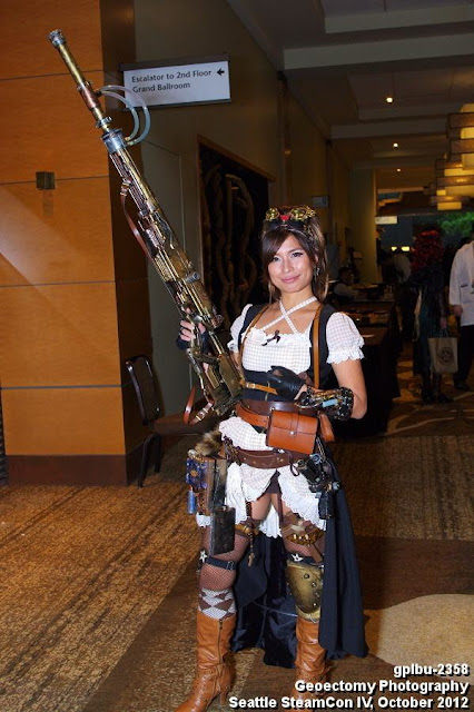 Woman wearing steampunk costume (gingham dress, boots, belt, goggles) with a big steampunk gun (steampunk weapon diy)