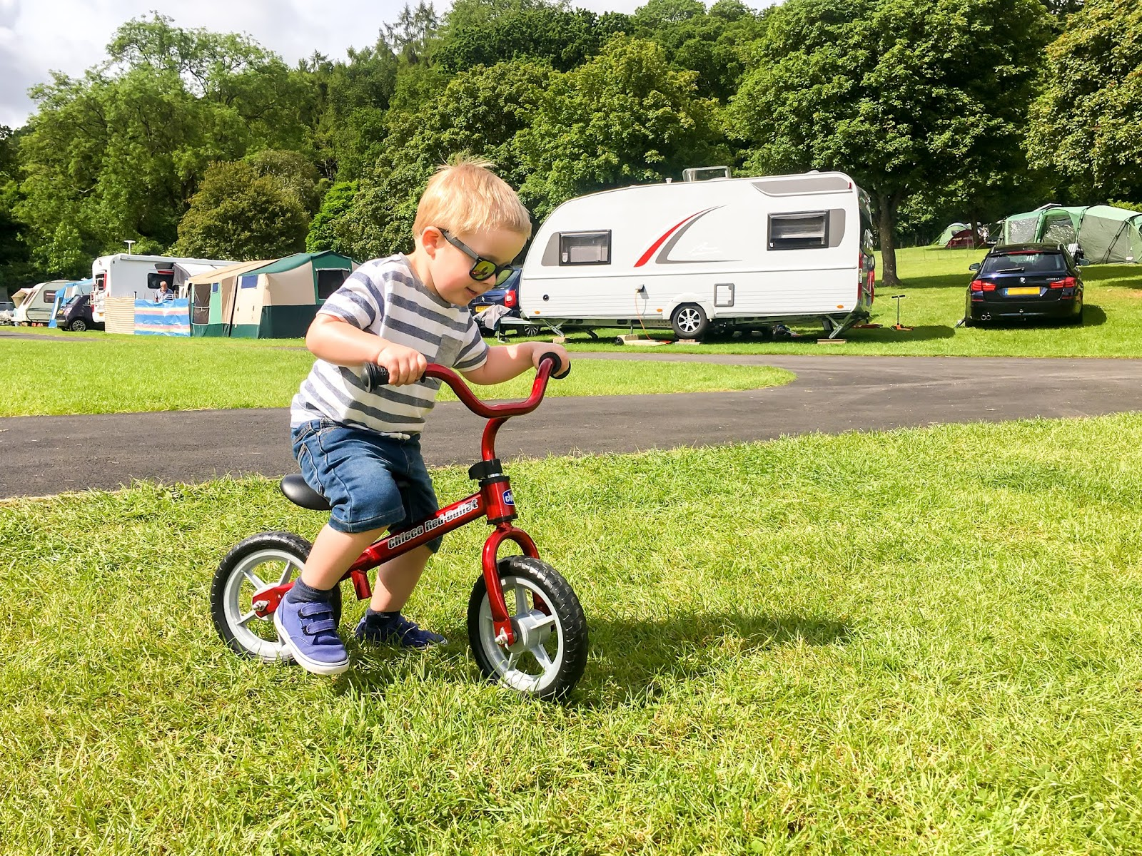 young boy wearing sunglasses and riding a red balance bike across a caravan site