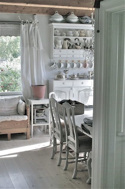 These vintage dishes and farmhouse curtains are stunning in this quaint and bright kitchen