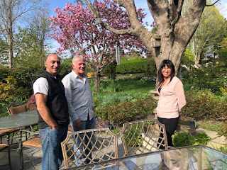 Smiling group of people in garden with cherry tree in bloom