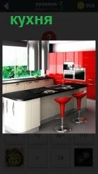 В помещении кухни находится стол со встроенной плитой, навесные шкафчики и красные стулья