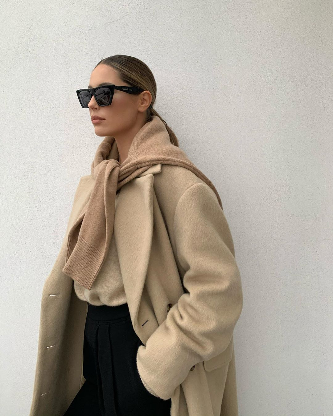 Minimalist Winter Outfit Idea — @mathildegoehler in square cat-eye sunglasses, a beige coat, camel sweater tied over the shoulders, and black pants
