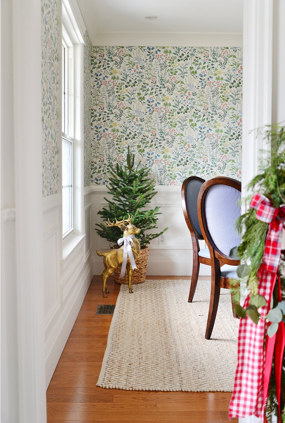 floral wallpaper in dining room, small christmas tree in basket, brass dear