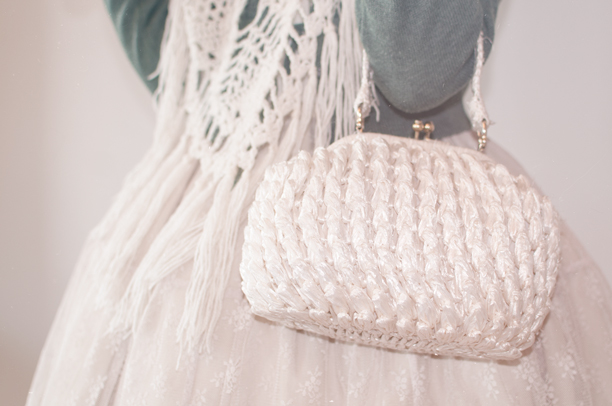 a detail shot of a lolita holding an ivory vintage bag