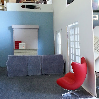 One-twelfth scale modern miniature lounge in soft blue, grey and red with a sectional sofa, a fireplace and french doors.