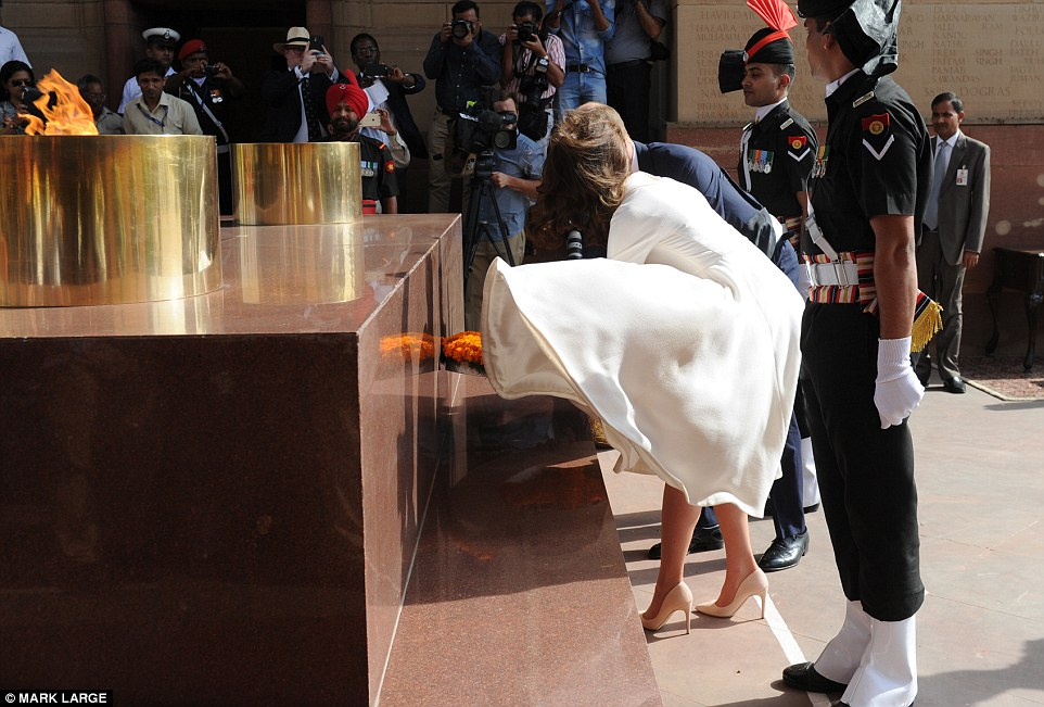 The Duke & Duchess of Cambridge lay a wreath while Kate struggles with her flapping dress
