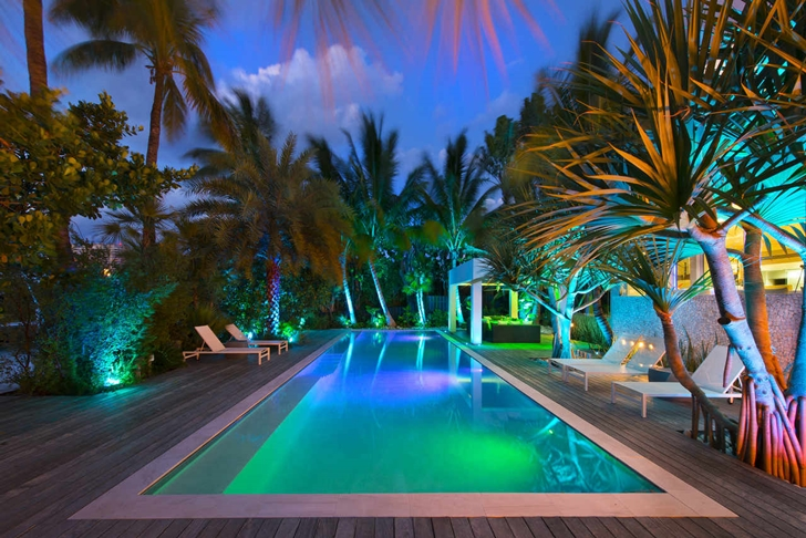 Large swimming pool in Modern mansion in Miami at night