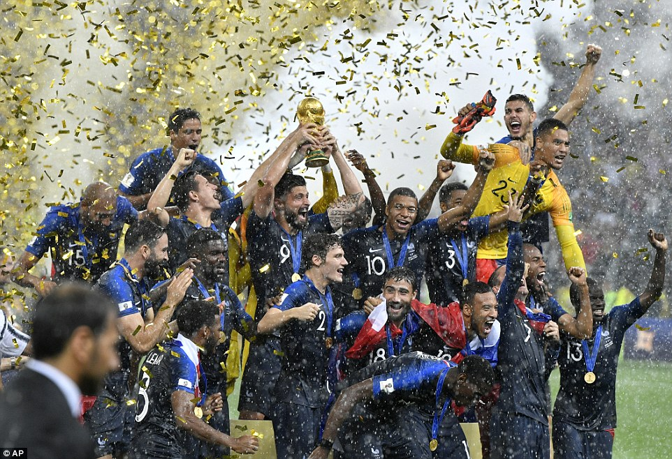 France's Olivier Giroud holds up the World Cup trophy as players celebrate winning the title for the second time today