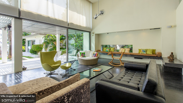 The inside of a villa with leather sofas and a rocking horse