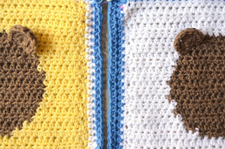 A close-up, top view of two squares side by side, yellow on the left and white on the right.  Only the vertical halves of each square can be seen showing one ear of each teddy face. The borders are alongside to show how the yellow square on the left has a border of one white row followed by a blue row while the white square on the right has a border of two blue rows.